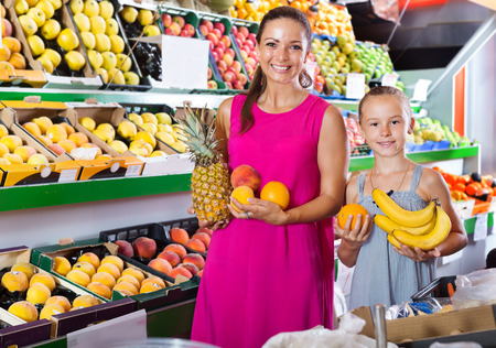 Positive mother with girl picking a different fruits at supermarket. Focus on both persons
