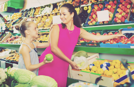 Smiling mother with girl picking aromatic apples at the fruit shop. Focus on both persons