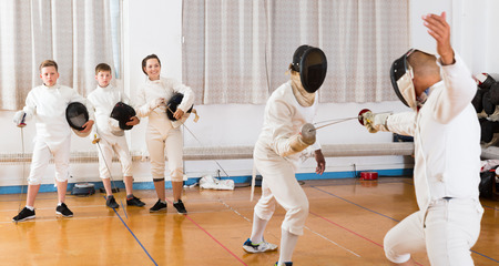 Two fencing instructors showing to young fencers effective techniques in training room