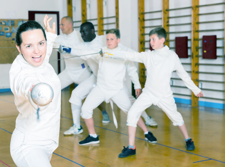 Young positive female training attack movements with rapier at fencing workout Stock Photo