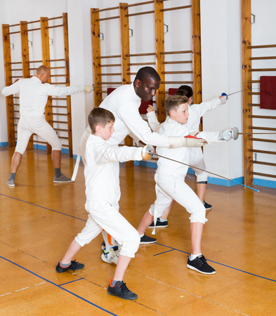 Fencing instructor explaining to young fencers effective movements and techniques at a training room Stock Photo