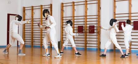 Positive group  practicing effective fencing techniques in sparring in training room