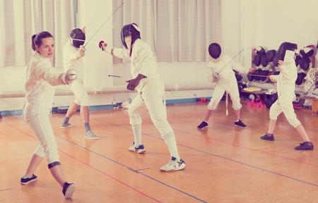 Portrait of emotional young woman wearing fencing uniform practicing with foil in the gym Stock Photo