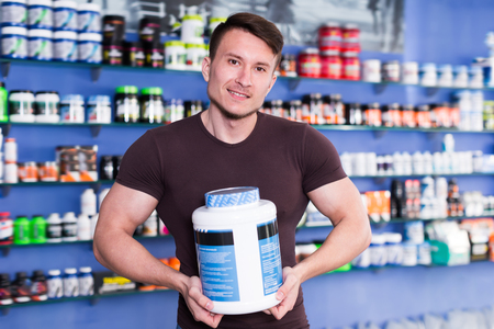 Portrait of positive guy with jars of sports nutritional supplements in store