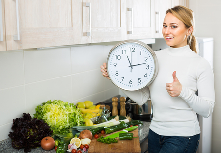Young blonde woman cooking vegetables and looking at clock at home kitchen