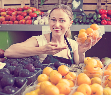 Cheerful positive beautiful young female seller wearing apron holding plums in fruit shop