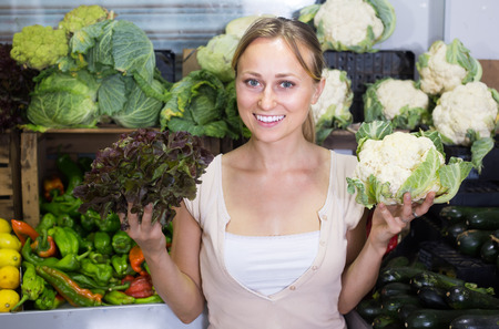 Portrait of cheerful smiling young woman buying fresh cabbage in fruit shop Imagens