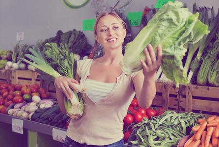 Portrait of positive cheerful woman shopping fresh green celery, leek and lettuce in shop Zdjęcie Seryjne