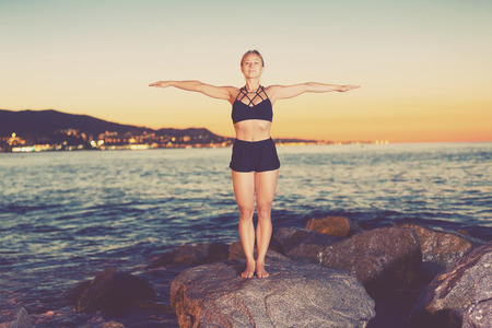 Woman is practicing stretching on a rock near sea at the dawn. Stock fotó