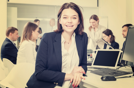 Portrait of happy attractive elegant girl in modern open plan office on background with coworkers