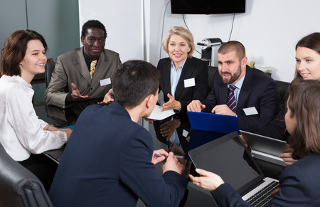 Multinational group of confident business colleagues planning work at joint meeting