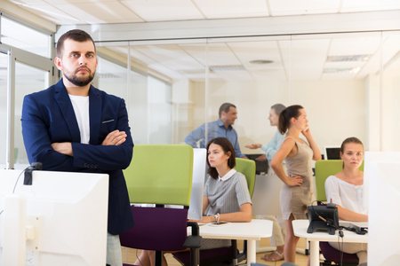 confident young businessman with arms crossed in busy modern coworking space