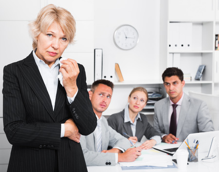 Business woman crying standing in office with working colleagues behind Stockfoto