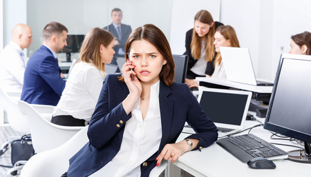Successful young cheerful positive business woman with phone relaxing at workplace in modern office