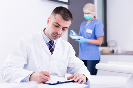 Confident doctor cosmetologist working with documents in modern cosmetic office Archivio Fotografico - 112403725