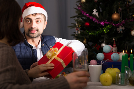 Young couple celebrating New Year at dinner, man in hat giving present to woman
