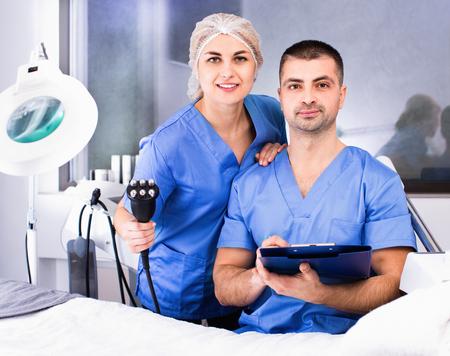 Porträt von zwei fröhlichen positiven professionellen Kosmetikerinnen im modernen medizinischen ästhetischen Büro Standard-Bild