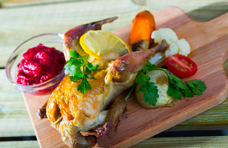Roasted partridge with cranberry sauce and garnish of grilled carrots, cauliflower, tomato and onion
