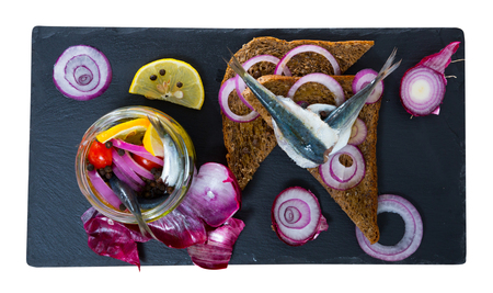Homemade pickled sprats with onions, beets, mix of peppers and marinade of vinegar, lemon, olive oil and sea salt. Served on rye bread with onion. Isolated over white background