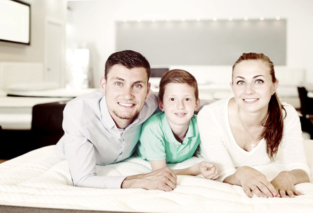 young family of three choosing right mattress in modern home furnishings store Stock fotó