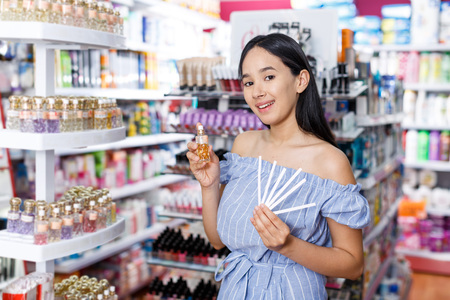 Stylish girl with testers in perfumery, choosing perfume in cosmetic shop