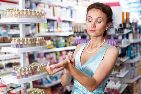 Stilvolle Frau im blauen Kleid, das in der Parfümerie einkauft und Parfüm wählt