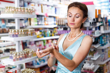 Stylish female in blue dress shopping in perfumery, choosing perfume