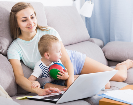 Satisfied woman with kid is productively working behind laptop at home.