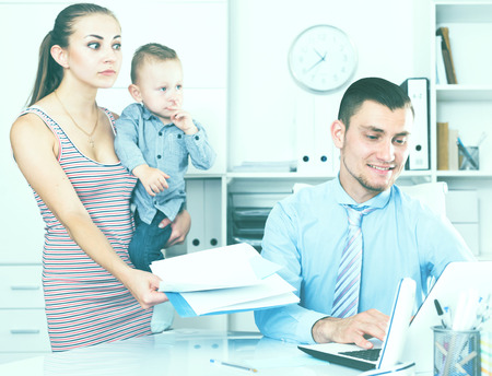 mother and little boy andadvising with adult banker worker in modern office Stockfoto