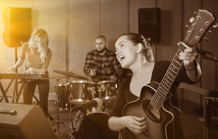 Attractive  smiling female soloist playing guitar and singing with her music band in sound studio