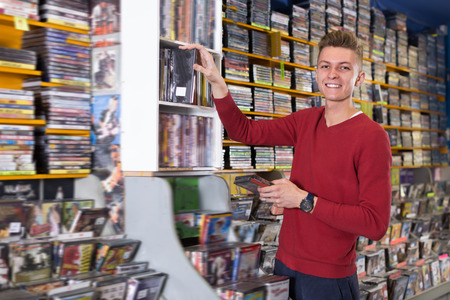 Adult man browsing contents on DVD cover choosing movies from diversity at store Foto de archivo