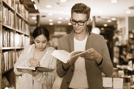 Young people spending time together reading  books in  library