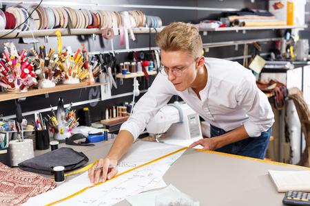 Professional male dressmaker at work – creating pattern at his workplace Reklamní fotografie