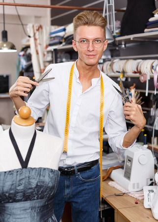 Portrait of happy blond male tailor at his workplace in sewing atelier