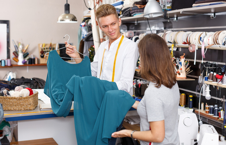 Professional male tailor showing customer dress at sewing atelier