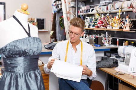 Young male fashion designer standing near tailor mannequin and taking papers in his hands