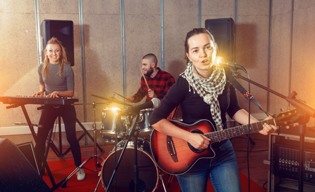 Attractive happy cheerful female soloist playing guitar and singing with her music band in sound studio