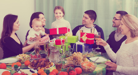 Relatives wishing little girl happy birthday and giving presents at festive table. Focus on girl Stockfoto