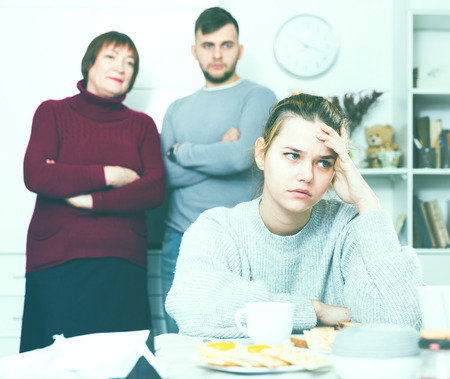 Young upset woman sitting separately having problems in relationship with husband and his mother