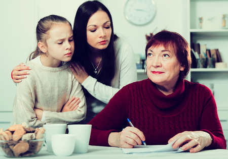 Serious senior woman signing documents while disgruntled daughter and granddaughter staring intently