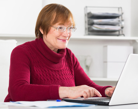 Senior female worker working productively on project in office