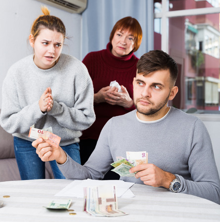 Frustrated man reluctantly giving cash to young wife standing with mother and begging more Reklamní fotografie