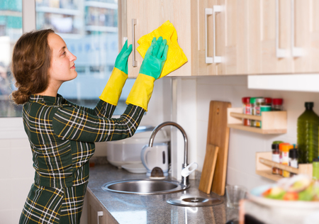 Young woman wearing protective yellow gloves cleaning kitchen surfaces Archivio Fotografico
