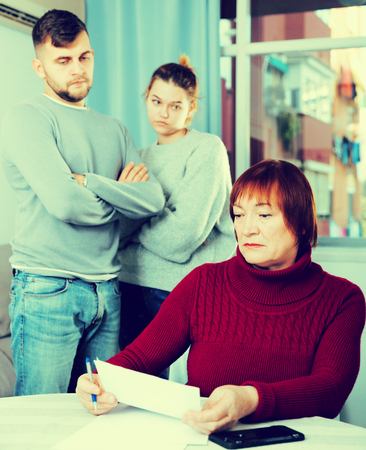 Dissatisfied man with his wife pointing to some paper to offended elderly mother