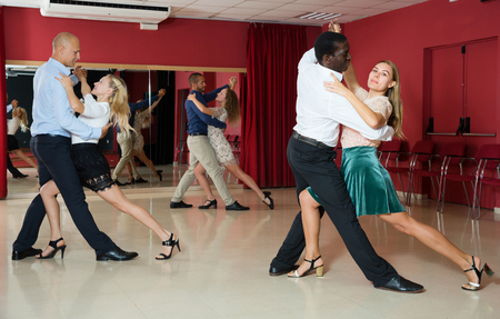 Portrait of positive adult pairs enjoying tango in modern dance hall together