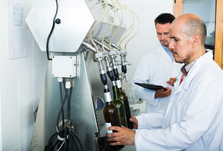 Mature man wearing white coat working on bottling equipment on wine making manufactory