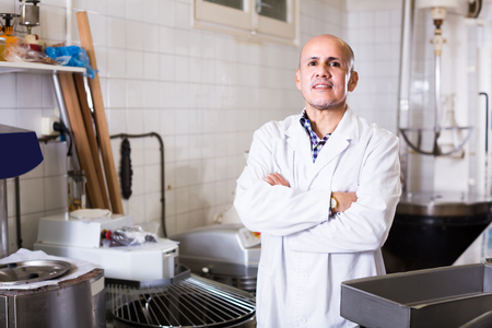 Portrait of positive russian mature man working in modern food factory