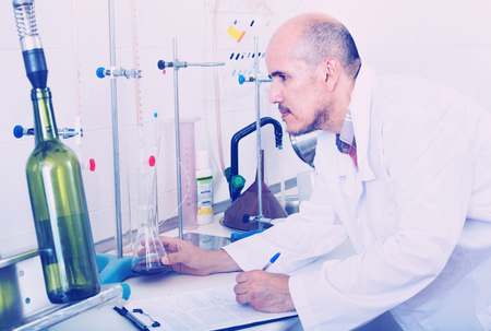 Attentive diligent pleasant mature man working on quality of products in winery lab Stock Photo