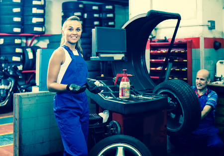 Young american female technician standing with wheel balancing machinery at auto workshop