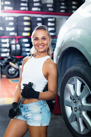 Young positive smiling woman holding tool in hands and working with auto in service point